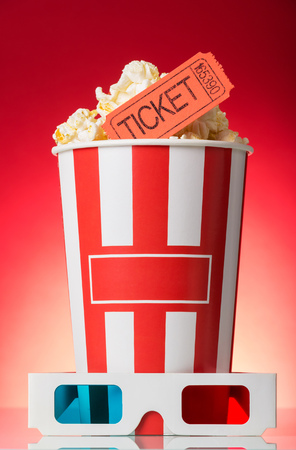 Box with popcorn and movie tickets, 3D glasses nearby on a bright red background.