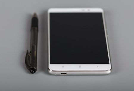 Modern multifunctional device and pen on gray background