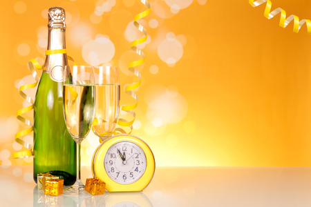 Waiting for the holiday, bottle of champagne and clock on  table background