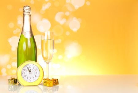 Bottle with champagne, small New Year surprises and clock on yellow background Stock Photo