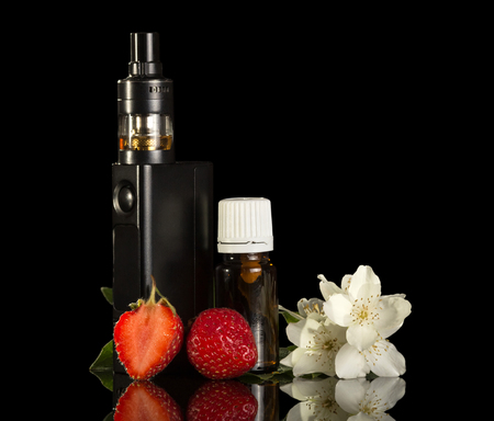 Electronic cigarette and liquid for smoking, strawberries isolated on black background