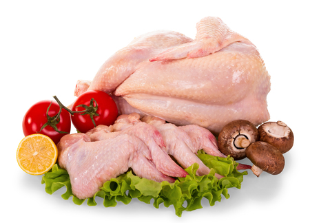 A whole raw chicken carcass and wings, tomatoes, mushrooms, lemon and lettuce leaves isolated on white background.