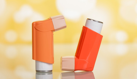 Two small pocket inhalers on yellow background