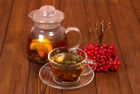 A jug with hot tea and bunch of viburnum from colds, on wooden table