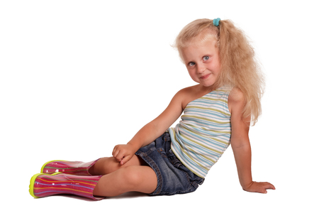 Seated charming little blond girl in a blouse, a skirt and rubber boots isolated on white background.