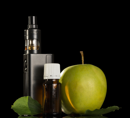 Device for inhaling aromatic liquids and an apple isolated on black background