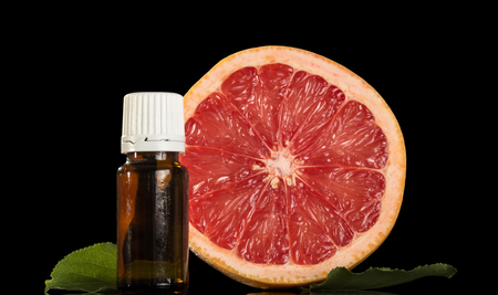 Liquid with a citrus aromafor for smoking an electronic cigarette, and piece of grapefruit isolated on black background Stock Photo