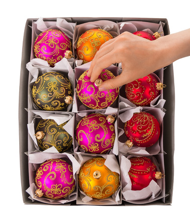womans hand: A womans hand takes bright, colorful New Years toys out of the box