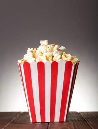 Striped square box filled with popcorn on gray background. Stock Photo