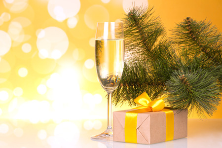 Fouger with champagne and box with gift on yellow sparkling background Stock Photo