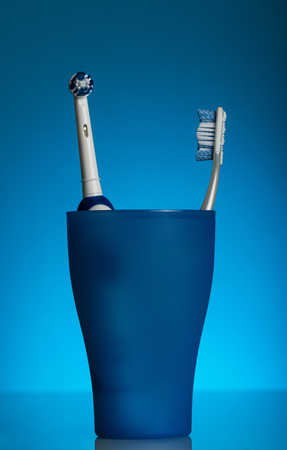 Two toothbrushes - manual and electric locate in a glass, on blue background