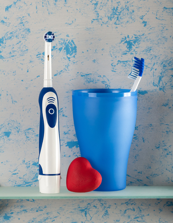 Electric, and usual toothbrush in glass, small heart, on blue background
