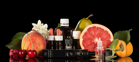 Electric cigarette, set of various liquids for smoking and fresh fruit isolated on black background