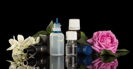 Electronic cigarette and a set of liquids for smoking with floral scent isolated on black background