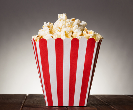 large square box filled with top popcorn on a gray background