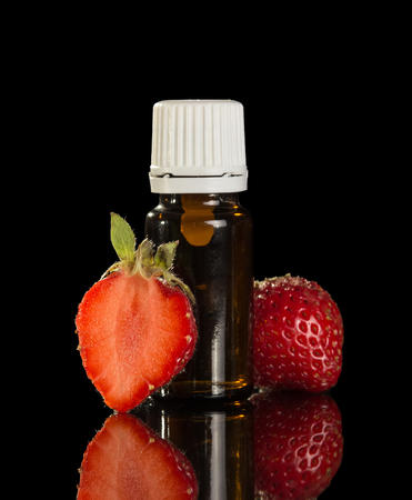 Liquid for inhaling pair of electronic cigarettes, and strawberries isolated on black background Stock Photo