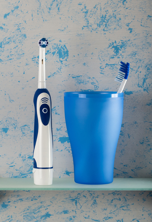 Electric and toothbrush in glass on bathroom shelf