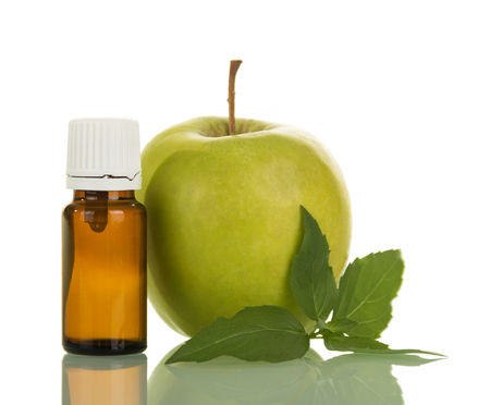 Bottle with liquid for smoking electronic cigarettes, and an apple, isolated on white background