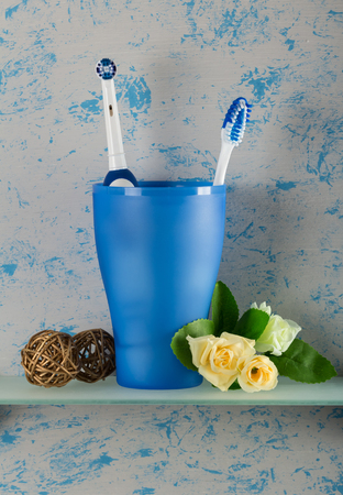 prophylaxis: In the glass there is an electric and manual toothbrush, beside the flowers, on glass shelf in bathroom Stock Photo
