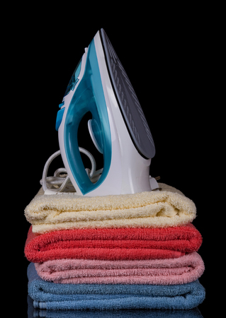 electric fixture: Modern electric iron stands on pile of terry towels, isolated on black background Stock Photo