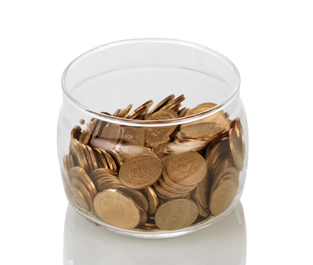 generosidad: Lots of coins collected in glass jar isolated on white background