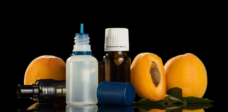 Liquid for Smoking with fruit flavor, electronic cigarette isolated on black background Stock Photo