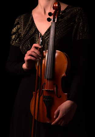 Violin and bow in the hands of the musician isolated on black background
