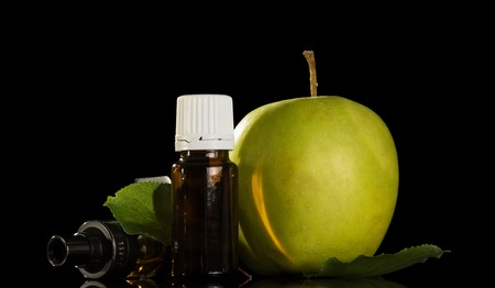 Bottle with liquid for smoking electronic cigarettes and ripe apple isolated on black background