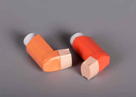 Two pocket inhalers for breathing on gray background