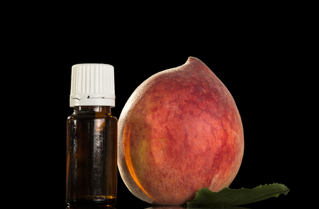 Big ripe peach and bottle of liquid for inhalation vapor electronic cigarettes, isolated on black background Stock Photo