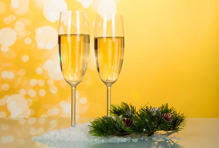 Two glasses of wine, pine branch with cones on artificial snow, on bright yellow background