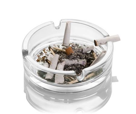 Estremità di sigaretta, ceneri, fiammiferi bruciati in un portacenere di vetro isolato su sfondo bianco. Avvicinamento