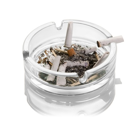 Cigarette butts, ashes, burnt matches in a glass ashtray isolated on white background. Close-up