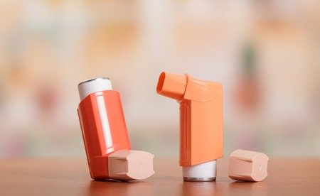 Two small pocket inhaler to relieve an asthma attack, located on table Stock Photo