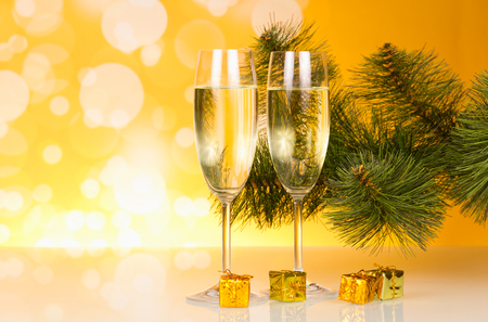 Champagne, Christmas pine twig and small gifts, on bright yellow background Stock Photo