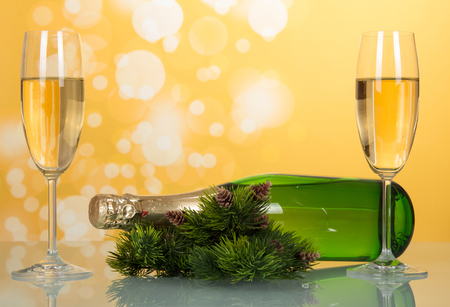 New year champagne bottle lies on the table near pine branches with pine cones and two full wine glass, on bright yellow background Stock Photo