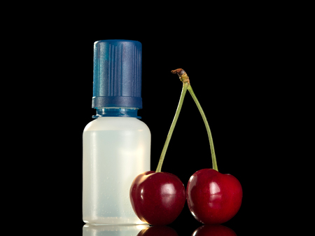 Bottle with liquid to inhaling flavored vapor electronic cigarette, two ripe cherries nearby, isolated on white background Stock Photo