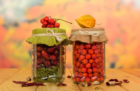 Banks with vitamin berries for future use, stand on wooden table Stock Photo