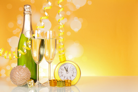Bottle of champagne, glasses, Christmas toys, gifts and clocks, on bright yellow background Stock Photo