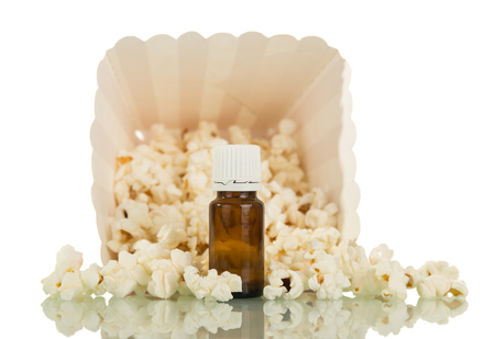 Bottle with liquid Smoking area, amid the spilled popcorn, isolated on white background