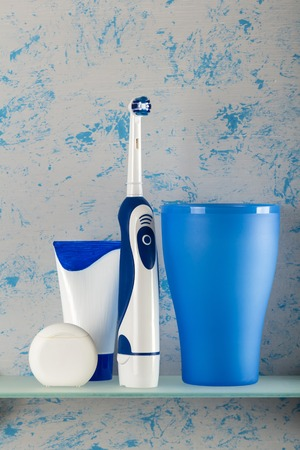 Electric toothbrush, toothpaste and dental floss on glass shelf