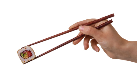 Hand of female keeps sushi rolls with wooden chopsticks isolated on white