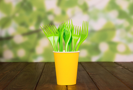 Disposable yellow forks stand in glass, on wooden table Stock Photo