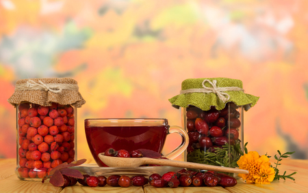 Banks with dry rosehip berries and mountain ash, cup of vitamin tea and saucer, on wooden table Standard-Bild