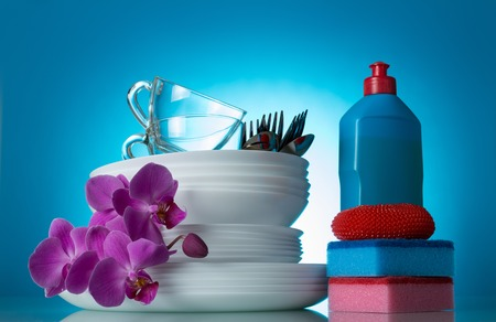 Set of clean dishes and Orchid flower, detergent, sponge, on blue Stock Photo