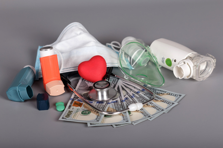 Inhalers and mask, stethoscope, money for diagnostics and treatment, on gray Stock Photo