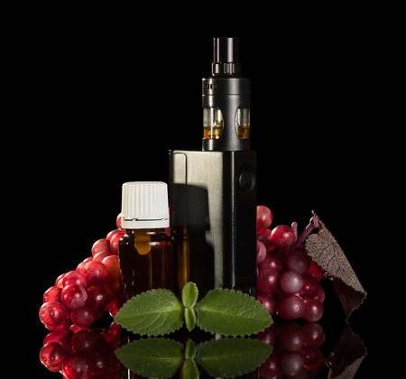 Electronic cigarette, liquid for Smoking, bunch of grapes and mint leaf isolated on black