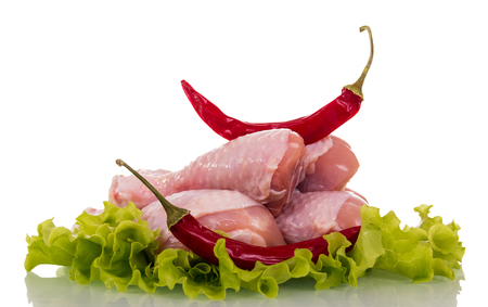 Chicken leg of raw birds on lettuce leaves and bitter red pepper isolated on white Stock Photo