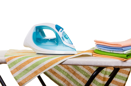Stack of clean towels and an iron on an ironing board isolated on white Stock Photo