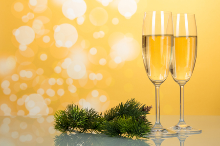 Glasses with champagne, new years pine branch on yellow background